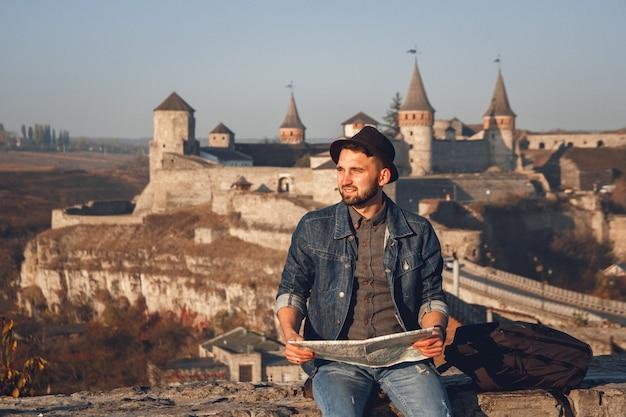 Reiziger man met een kaart in zijn handen zit op de achtergrond van het oude kasteel