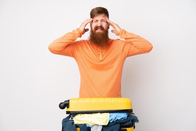 Reiziger man met een koffer vol kleren over geïsoleerde witte muur ongelukkig en gefrustreerd met iets. negatieve gezichtsuitdrukking