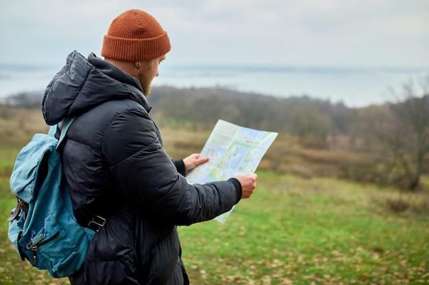 Reiziger man met rugzak met kaart in de hand op een achtergrond van bergen rivier van de natuur, reisconcept, vakanties en lifestyle wandelconcept