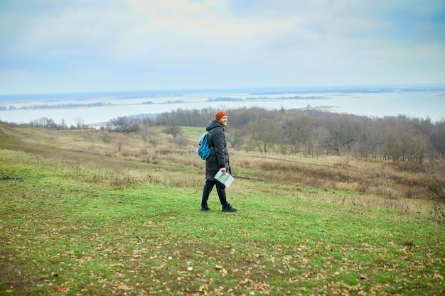 Reiziger man met rugzak met kaart in de hand op een achtergrond van bergen rivier van de natuur