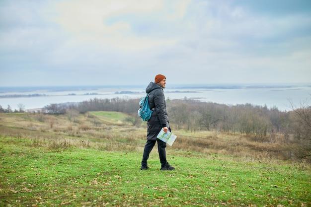 Reiziger man met rugzak met kaart in de hand op een muur van bergen rivier van de natuur, reisconcept, vakanties en levensstijl wandelconcept