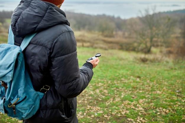 Reiziger man met rugzak met kompas in de hand op een muur van bergen rivier van de natuur, reisconcept, kampeertrip, gps, oriëntatieloop, navigator