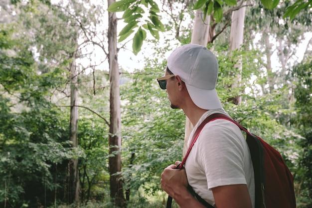 Reiziger man met rugzak wandelen in esdoornbos