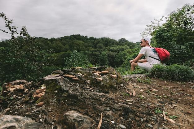 Reiziger man met rugzak zit en kijkt naar het bos voor hem
