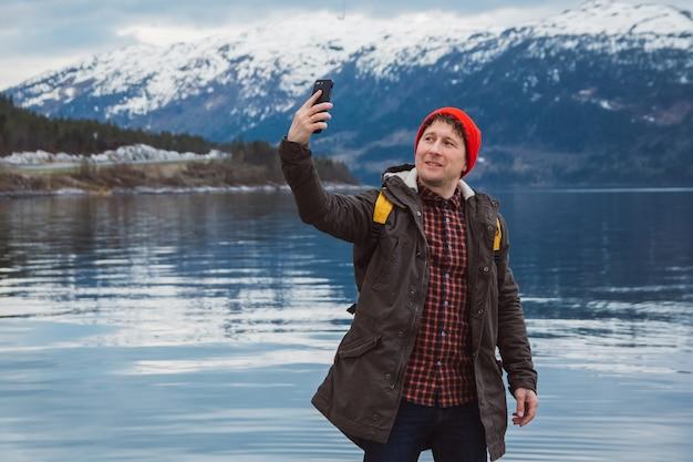 Reiziger man neemt zelfportret een foto met een smartphone de achtergrond van berg en meer