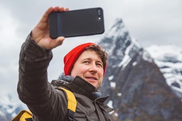 Reiziger man neemt zelfportret een foto met een smartphone staande op een achtergrond van een berg