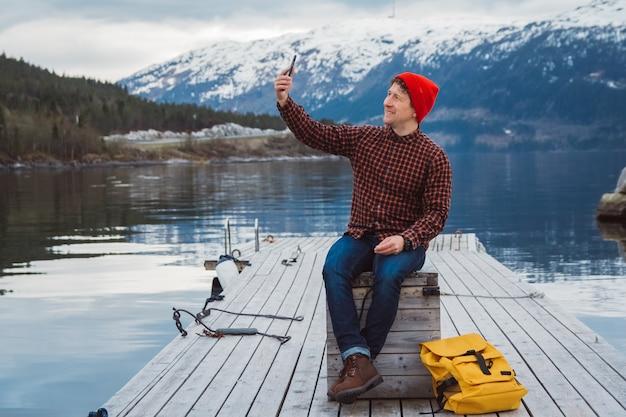 Reiziger man neemt zelfportret een foto met een smartphone zittend op een houten pier