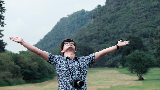 Reiziger man ontspannen met hoed en zonnebril, uitgestrekte armen staan op groene natuur achtergrond