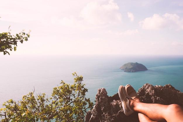 Reiziger man wandelen canvas schoenen dichtbij oceaan op aard achtergrond.