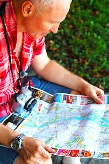 Reiziger man zit in het stadscentrum en bestudeert een kaart van boedapest.