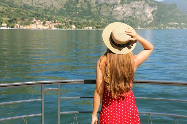 Reiziger meisje genieten van uitzicht op het comomeer. achteraanzicht van het jonge vrouw ontspannen op terras in bellagio, comomeer, italië. Premium Foto