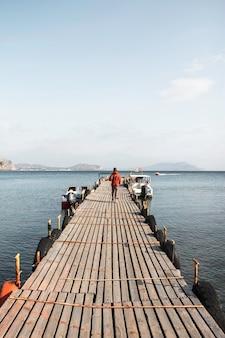 Reiziger meisje loopt langs een pier op de achtergrond van grote en prachtige bergen. novy svet, de krim. heldere zonnige dag. wandelen, reizen, vrijheid, levensstijlconcept.