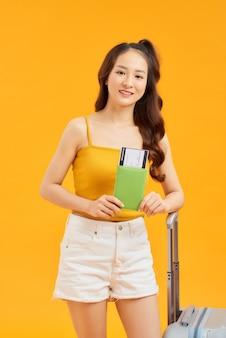 Reiziger meisje poseren geïsoleerd over oranje muur