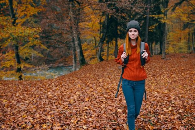 Reiziger met een rugzak in het herfstbos en hoed, trui, jeans, gevallen bladeren, bomen van het meer