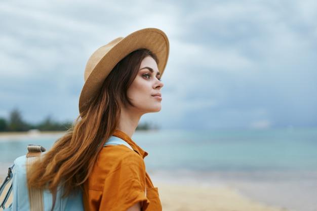 Reiziger met een rugzak op zijn rug met een hoed op het landschap van het natuureiland