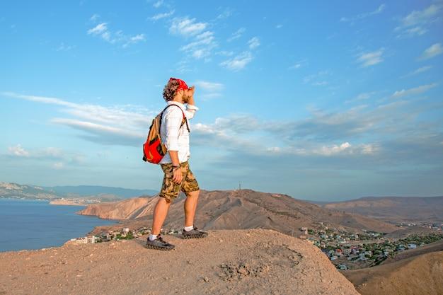 Reiziger met een rugzak op zijn rug staat op de top van een berg en bewondert het landschap