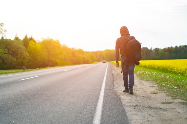 Reiziger met grote rugzak op zijn rug loopt langs de weg aan de kant van de weg