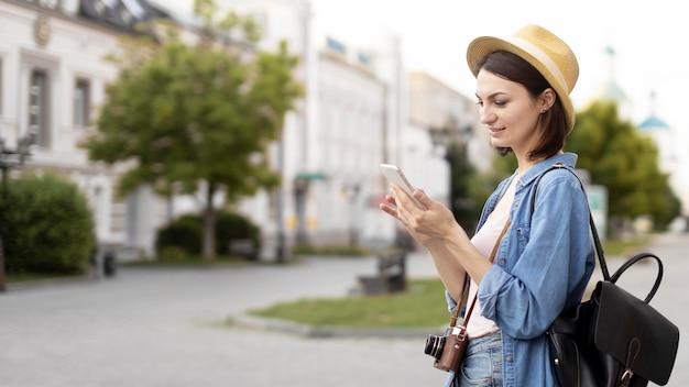 Reiziger met hoed die mobiele telefoon doorbladert