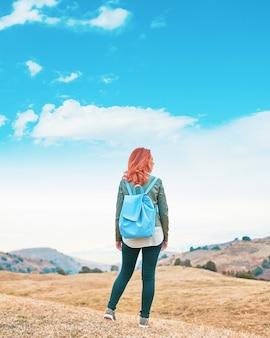 Reiziger met rugzak kijkt uit naar bergen