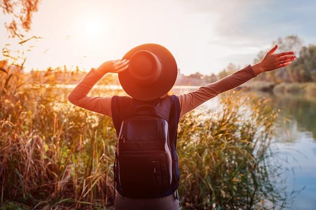 Reiziger met rugzak ontspannen door lente rivier bij zonsondergang. jonge vrouw hief haar armen op en voelde zich vrij en gelukkig. actieve levensstijl
