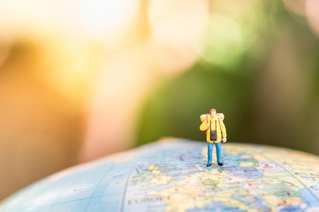 Reiziger miniatuur minifiguren met rugzak staan en lopen op globe wereldkaart ballon