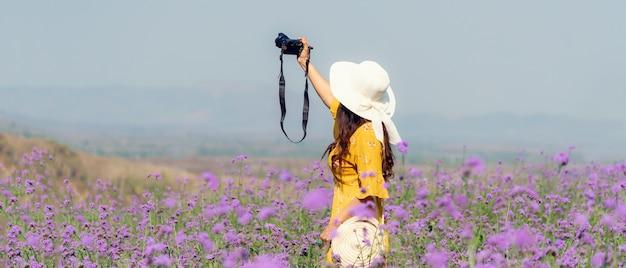 Reiziger of toerisme aziatische vrouwen staan en houden camera nemen een fotobloem in het paarse verbena veld