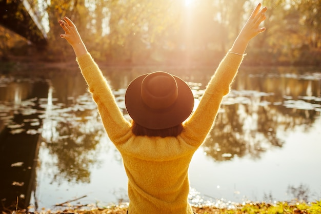 Reiziger ontspannen door herfst rivier bij zonsondergang. gelukkige vrouwentoerist die op bank zit die wapens opheft die vrij voelen. herfstactiviteiten