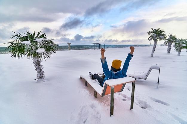 Reiziger ontspannen op een ligstoel tussen groenblijvende tropische palmbomen bedekt met sneeuw