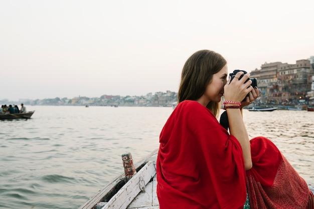 Reiziger op een boot die foto's maakt van de rivier de ganges