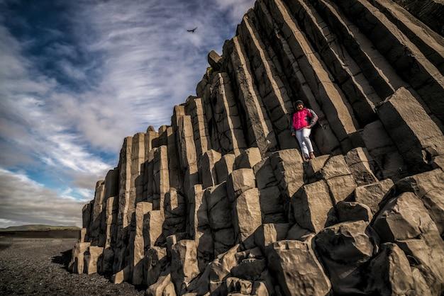 Reiziger op zeshoekige rotsen in vik, ijsland.
