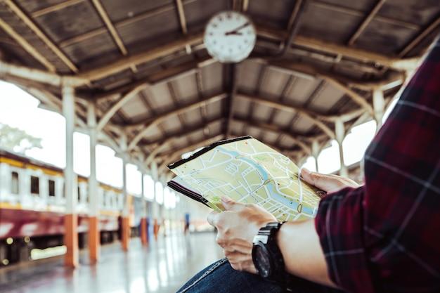 Reiziger op zoek naar de kaart tijdens het wachten op de trein op treinstation. reizen concept. man reizen