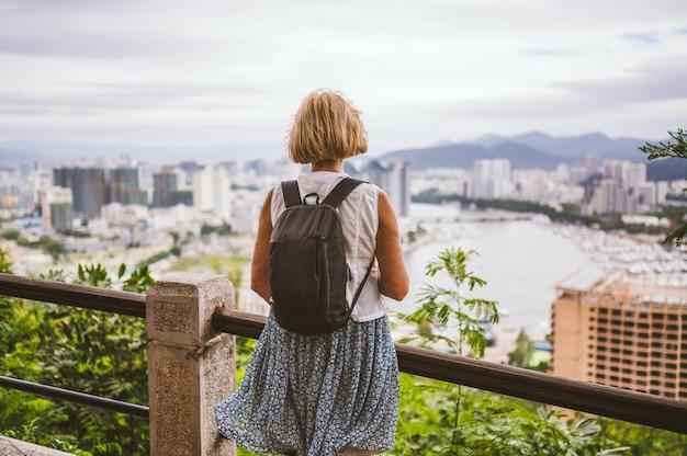 Reiziger oudere backpacker vrouw nemen van foto's met uitzicht op de binnenstad. reisavontuur in china, toeristische mooie bestemming azië, zomervakantie vakantiereis. vrijheid en gelukkige mensen concept