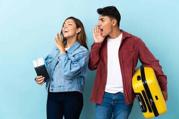 Reiziger paar met een koffer op blauw schreeuwen met mond wijd open naar de zijkant