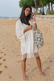 Reiziger schattige aziatische vrouw in witte jurk wandelen op het tropische strand. mooie vrouw die van vakanties geniet