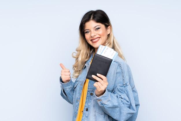 Reiziger tiener met een koffer geïsoleerd op blauwe muur in vakantie met een paspoort en een vliegtuig met duim omhoog