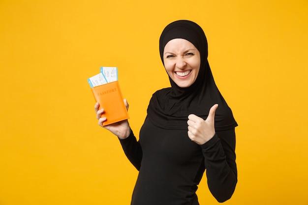 Reiziger toeristische jonge arabische moslimvrouw in hijab zwarte kleding houdt paspoort tickets geïsoleerd op gele muur portret. mensen religieuze levensstijl concept.