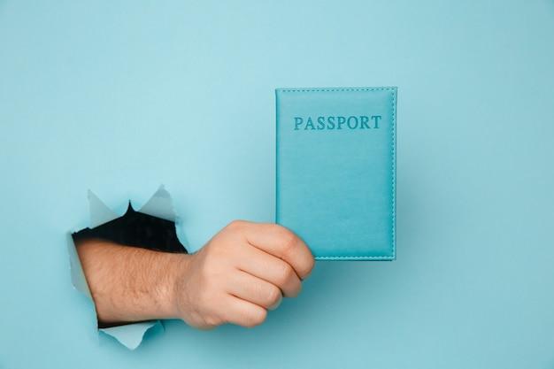 Reiziger toeristische man hand houden paspoort uit een gescheurd gat in blauw papier