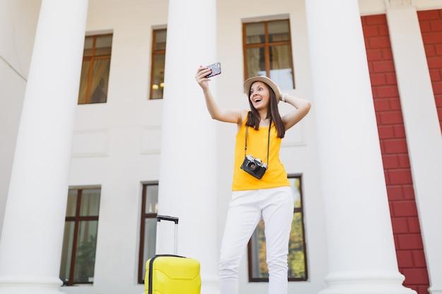 Reiziger toeristische vrouw doet selfie schot praten op mobiele telefoon, vriend bellen, taxi boeken, hotel op mobiele telefoon buiten. meisje op weekendje weg naar het buitenland. toeristische reis levensstijl.