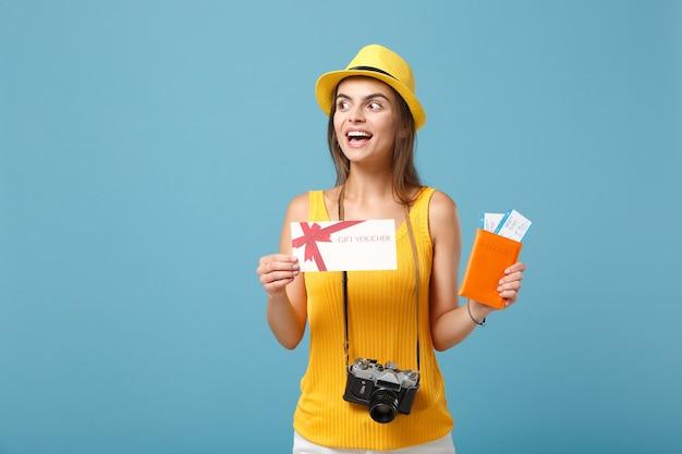 Reiziger toeristische vrouw in gele vrijetijdskleding hoed met kaartjes cadeaukaart camera op blauw