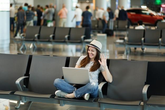 Reiziger toeristische vrouw in hoed die op laptop werkt, zwaaiend met de hand voor begroeting in web-camera tijdens videogesprek, wachtend in de lobby op de luchthaven