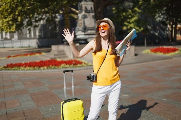 Reiziger toeristische vrouw in oranje hart bril met koffer, stadsplattegrond, retro vintage fotocamera spreidende handen in de stad buiten. meisje op weekendje weg naar het buitenland. toeristische reis levensstijl.