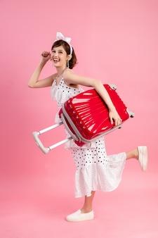 Reiziger toeristische vrouw in zomer vrijetijdskleding met reizen koffer geïsoleerd op roze
