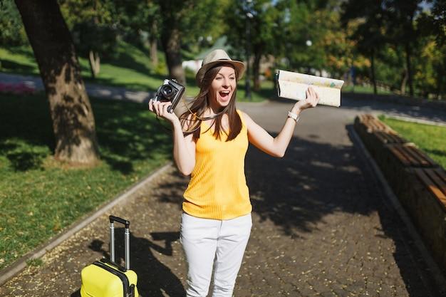 Reiziger toeristische vrouw met koffer stadsplattegrond met retro vintage fotocamera spreidde handen schreeuwend in de stad buiten. meisje dat naar het buitenland reist om een weekendje weg te reizen. toeristische reis levensstijl.