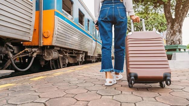 Reiziger toeristische vrouw wandelen en slepen bagage tas op treinstation en hotel zoeken voor het boeken van kamer.