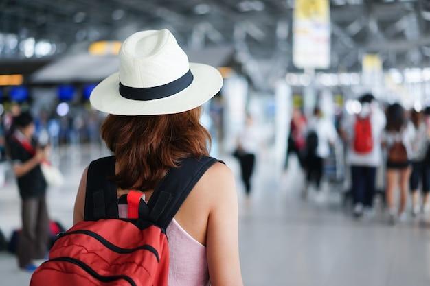 Reiziger vrouw draagt hoed en draagtas permanent binnen luchthaven na check-in vlucht