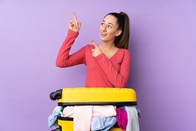 Reiziger vrouw met een koffer vol kleren over geïsoleerde paarse muur wijst met de wijsvinger een geweldig idee