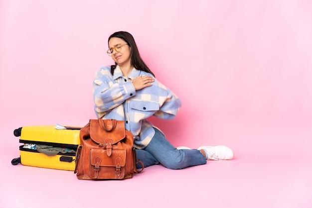 Reiziger vrouw met een koffer zittend op de vloer die lijdt aan pijn in de schouder omdat ze zich heeft ingespannen
