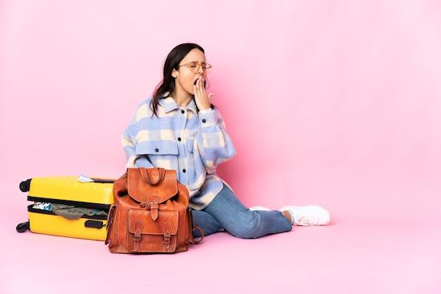 Reiziger vrouw met een koffer zittend op de vloer geeuwen