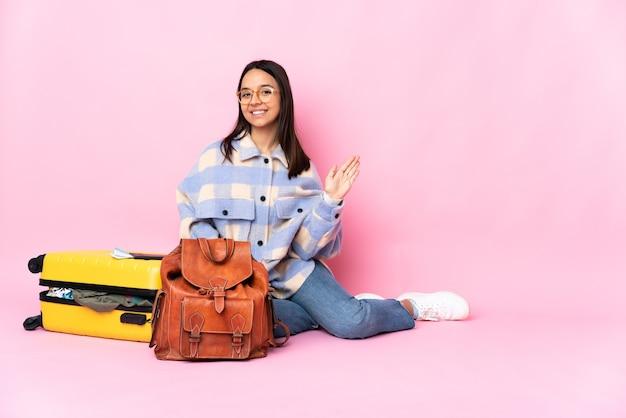 Reiziger vrouw met een koffer zittend op de vloer groeten met hand met gelukkige uitdrukking