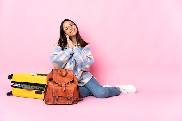 Reiziger vrouw met een koffer zittend op de vloer houdt de handpalm bij elkaar. personen voor iets